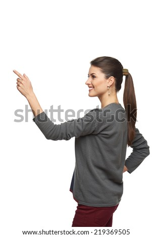 Side view of young woman in cardigan pointing at copy space, isolated on white