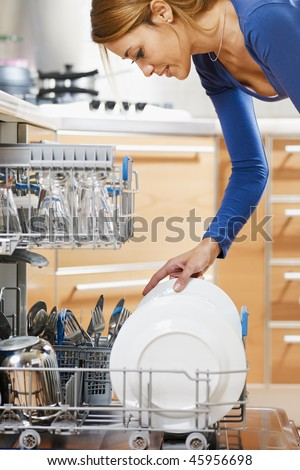 side view of young woman in kitchen doing housework - stock photo