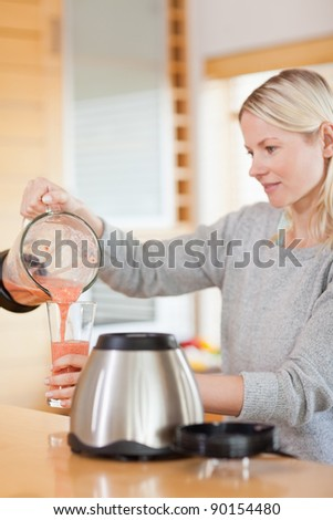 Side view of young woman pouring self made smoothie - stock photo
