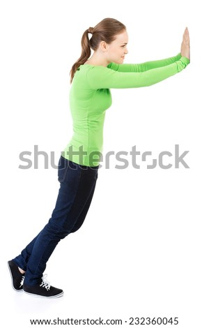 Side view of young woman pushing an abstract wall. - stock photo