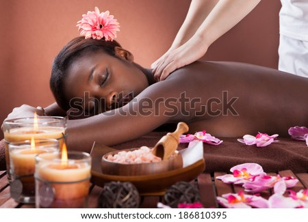 Side view of young woman receiving shoulder massage at spa salon - stock photo