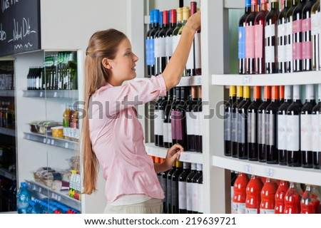 Side view of young woman shopping for alcohol at supermarket - stock photo