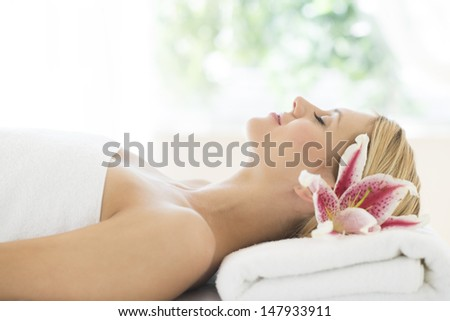 Side view of young woman sleeping on massage table in health spa - stock photo