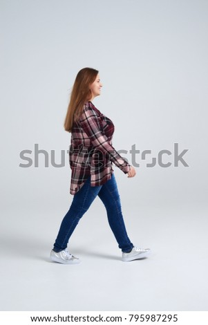 Side view of young woman walking in shirt and jeans