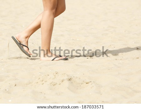 Side view of young woman walking on beach with flip flops - stock photo