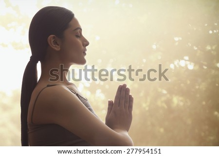 Side view of young woman with hands clasped meditating against trees - stock photo
