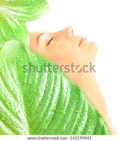 Side view on beautiful woman with closed eyes covered big fresh green leaves with dew drops isolated on white background, enjoying day spa - stock photo