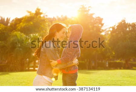 Side view on cheerful mother and daughter looking on each other, playing in the park in spring sunny day, happy family life - stock photo