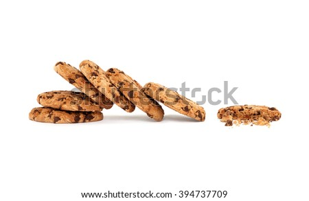 Side view on collapsed stack of six yummy chocolate chip cookies next to a partially eaten one with crumbs, isolated on white background with copy space - stock photo