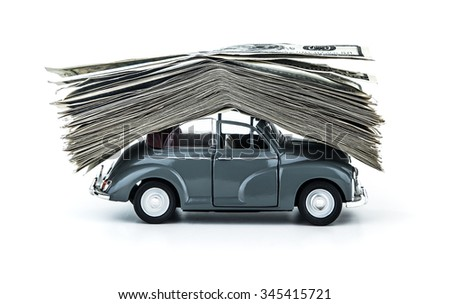 Side view on small decorative car model carries on itself a lot of cash isolated on white background, dollars of USA, credit for car concept  - stock photo