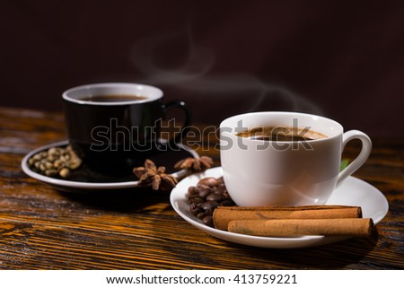 Side view on steaming hot black and white cups of coffee with beans and herbs in saucer on wooden table