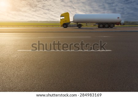 Side view on tank truck in motion blur on highway towards the setting sun. - stock photo