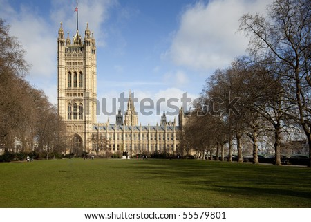 Side view on the British Parliament with a large meadow with green grass in front of it - stock photo