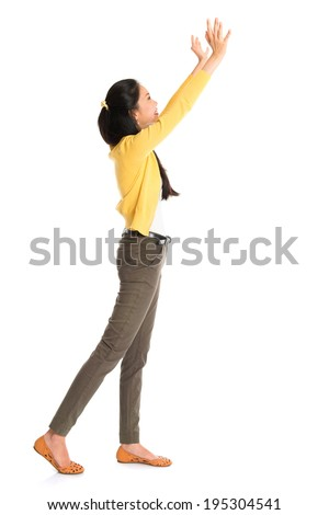 Side view or profile of an Asian girl arms up like pushing something away, full length standing isolated on white background. - stock photo