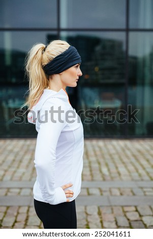 Side view pf young sporty woman standing with her hands on hips outdoors. Caucasian female athlete on street preparing for a city run. - stock photo