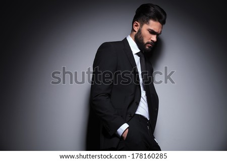 side view photo of a young fashion man holding his hands in his pockets and looking down, away from the camera with a sad expression. on a dark background - stock photo