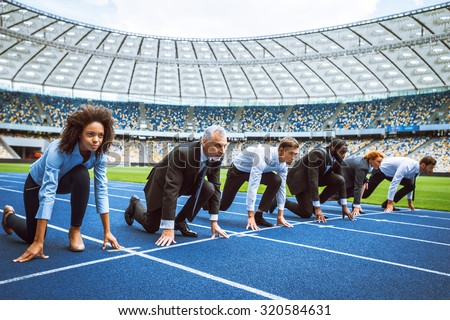 Side view photo of confident multi ethnic business people lined up getting ready for race on modern sport track. Stadium as a background - stock photo