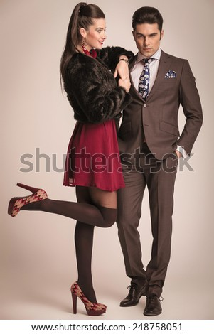 Side view picture of a beautiful young woman looking at her lover while leaning on him and lifting one leg up. - stock photo