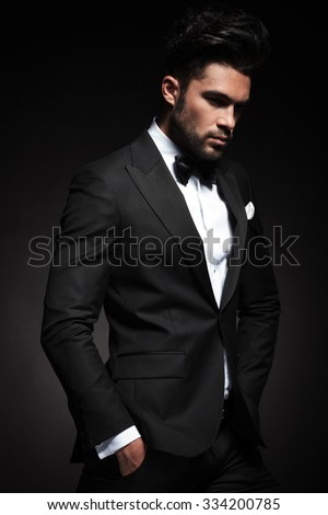 Side view picture of a elegant business man posing on black background with both hands in his pocket. - stock photo