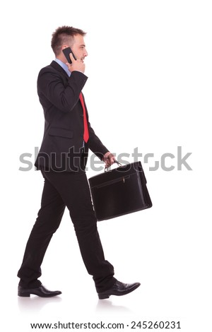 Side view picture of a handsome business man walking on studio backgound while talking on the phone. - stock photo