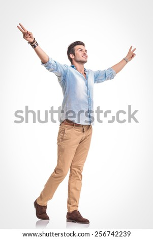 Side view picture of a handsome young fashion man walking with both hands in up, celebrating a victory. - stock photo