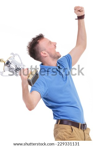 side view picture of a young casual man holding a trophy and shouting while looking up. isolated on a white background - stock photo