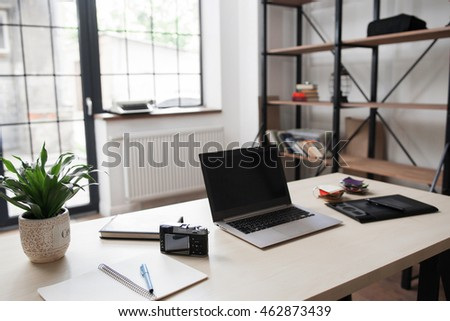 Side view picture of studio workplace with blank laptop. Web designer, photographer, retoucher comfortable work table, home office