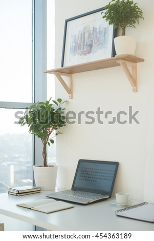 Side view picture of studio workplace with blank notebook, laptop. Designer comfortable work table, home office. - stock photo
