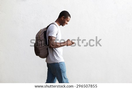 Side view portrait of a african american student walking with bag and mobile phone - stock photo