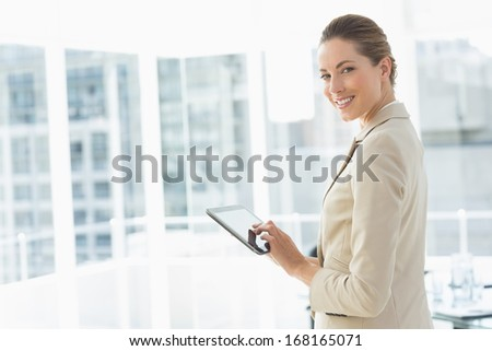 Side view portrait of a beautiful young businesswoman using digital tablet in a bright office