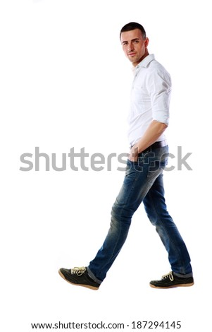 Side view portrait of a casual man walking over white background - stock photo
