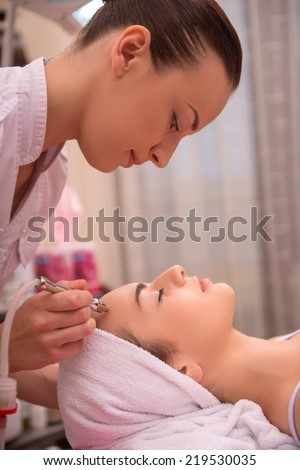 Side-view portrait of a cosmetologist and a young woman with a towel on her head lying on a table with closed eyes getting a laser skin treatment in healthy beauty spa salon - stock photo