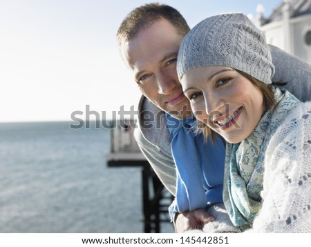 Side view portrait of a couple on pier against the sea - stock photo