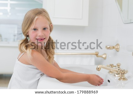Side view portrait of a cute girl washing hands at washbasin in the bathroom