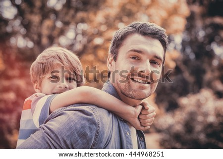 Side view portrait of a father carrying young boy on back at the park - stock photo