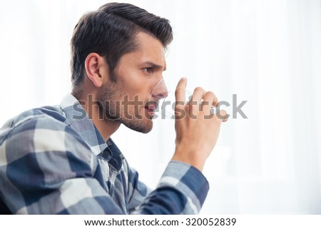 Side view portrait of a handsome man drinking water isolated on a white background - stock photo