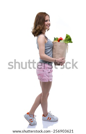 Side view portrait of a happy woman holding a shopping bag full of groceries - stock photo