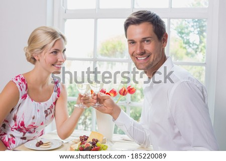 Side view portrait of a happy young couple toasting wine glasses over food at home - stock photo
