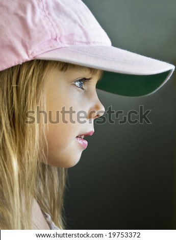 side view portrait of a little girl, model in pink cap