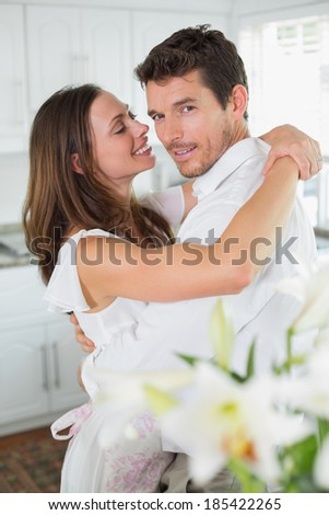 Side view portrait of a loving young couple embracing at home - stock photo