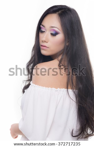 Side view portrait of a model with long and black hair isolated over white background