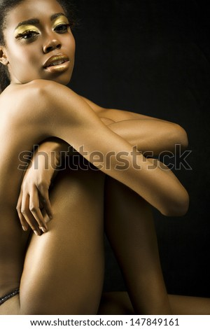 Side view portrait of a nude African American woman with golden makeup against black background - stock photo
