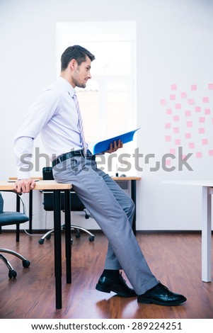 Side view portrait of a pensive businessman leaning on the table with folder - stock photo