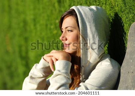 Side view portrait of a pensive teenager skater girl thinking with a green blurred background - stock photo