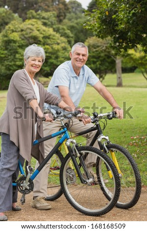 Side view portrait of a senior couple on cycle ride in countryside - stock photo