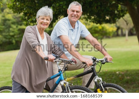 Side view portrait of a senior couple on cycle ride in countryside