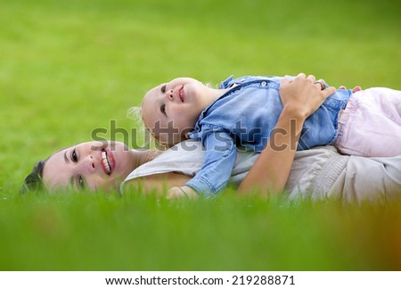 Side view portrait of a smiling mother lying down on grass with cute baby - stock photo