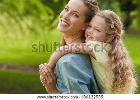 Side view portrait of a woman carrying young girl at the park - stock photo
