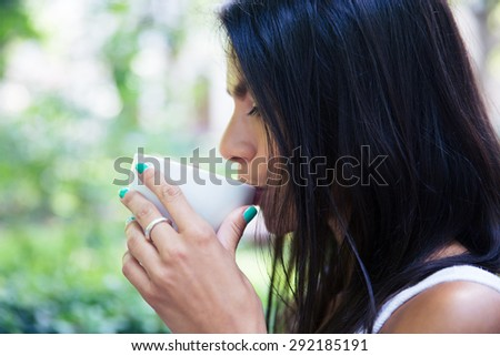 Side view portrait of a woman drinking coffee outdoors - stock photo