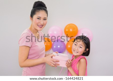 Side view portrait of a woman giving gift box to a little girl at a birthday party